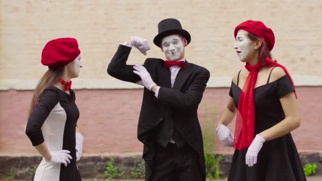 Mimes make perfomance near building Company of three mimes, man and women in black dress do perfomance near building. Man shows his muscles and girls do not like and make jokes. Performance of street artists. Portrait of comics playing with facial expressions and gestures. greasepaint stock videos & royalty-free footage