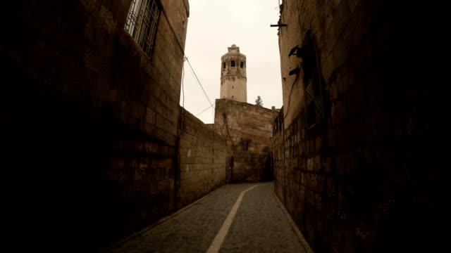 Minaret of Old Mosque Tower Above Narrow Ancient Stone Street Urfa video