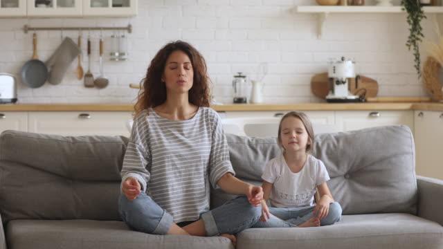 vídeos y material grabado en eventos de stock de mente mamá enseñando niña hija meditar juntos en el sofá - copiar