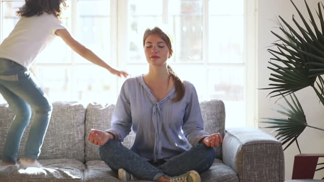 Mindful single mother meditating on sofa while active child jumping Mindful single mother meditating sitting on sofa while active energetic child daughter jumping playing, calm young mom doing yoga exercise at home for stress relief relaxing with naughty little kid mindfulness stock videos & royalty-free footage