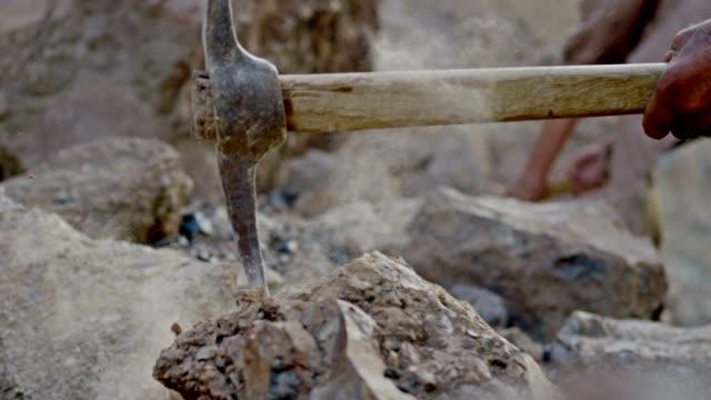 vidéos et rushes de mineur ou creuseur d'or brisant la roche en creusant la hache. fermez-vous vers le haut de la pioche frappant des roches.  tourné sur red epic dragon cinema camera au ralenti. - roc