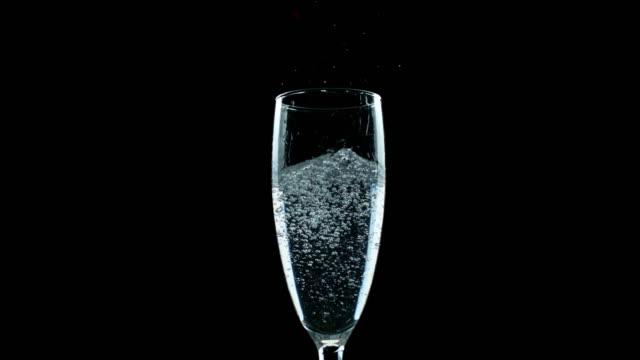 vidéos et rushes de slo mo ld eau minérale dans un verre de flûte - flûte à champagne