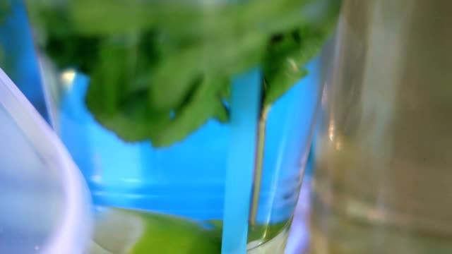 Mineralwasser im Glas mit Eiswürfeln, Minze, Limette und Zitrone Scheiben auf street Food festival – Video