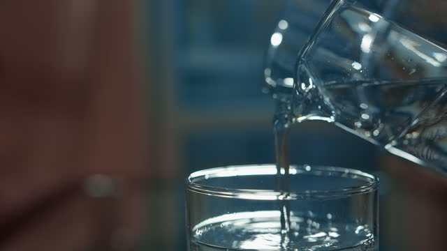 mineral water is poured into a glass from a decanter close up, moving camera video