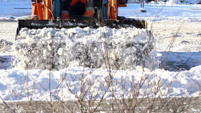 mini excavator working on street, cleaning snow. 4K