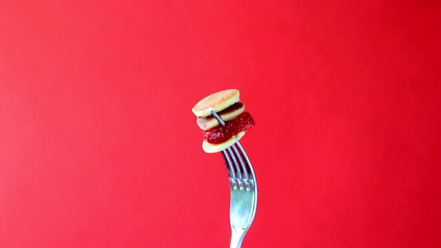 mini pannkaksflingor med jordgubbe på en gaffel snurrar runt på röd bakgrund - gaffel bildbanksvideor och videomaterial från bakom kulisserna