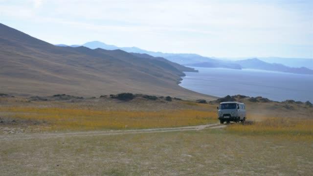 vídeos de stock e filmes b-roll de mini van driving cross the road in olkhon island, irkutsk russia - irkutsk