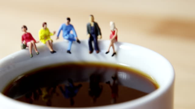 Miniature business people sitting on the edge of the coffee cup video