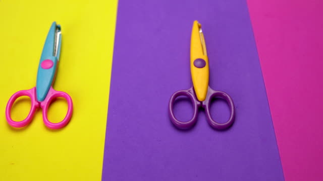 minimal background with moving colorful wavy blade scissors. - forbici video stock e b–roll