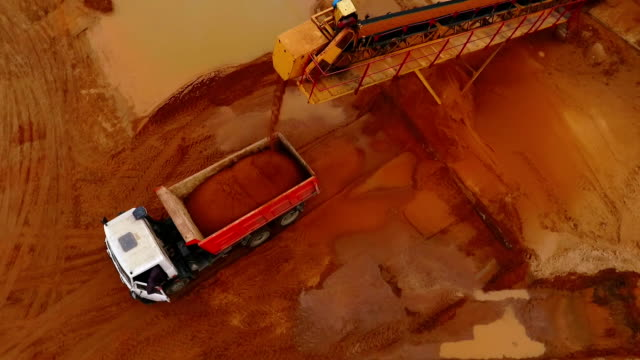 Mining conveyor loading sand in dumper truck. Aerial view of sand mining process Mining conveyor loading sand in dump truck. Sand work. Mining conveyor belt pouring sand in dump truck at quarry. Mining industry. Aerial view of sand mining process crane construction machinery stock videos & royalty-free footage