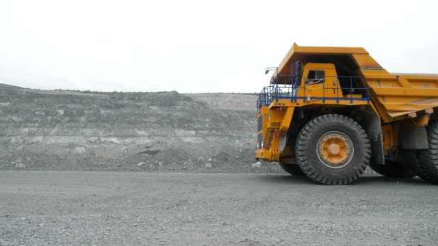 Mining dump truck is moving on a quarry road. Close-up video