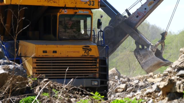 Mining DumpTruck rides against of an excavator Mining DumpTruck rides against of an excavator construction vehicle stock videos & royalty-free footage
