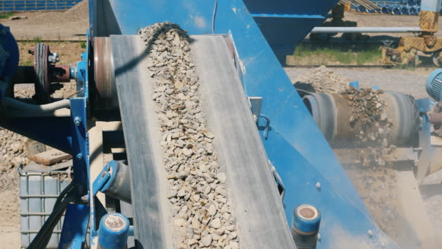 Mining industry concept. Crushing machine moves big stones on a conveyor.