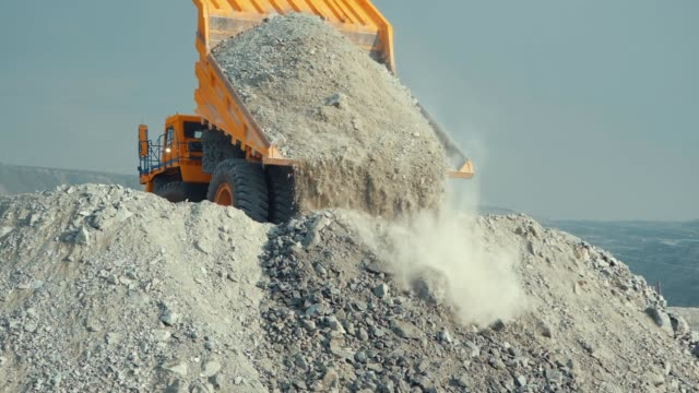 mining loader unloads limestone ore or rock. view from the back - ghiaia video stock e b–roll
