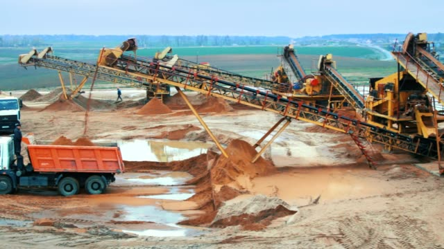 Mining site with heavy industrial equipment. Mining elevator with belt conveyor Mining site with heavy industrial equipment. Mining elevator with belt conveyor loading sand in dumper truck. Heavy machinery in mining industry construction vehicle stock videos & royalty-free footage