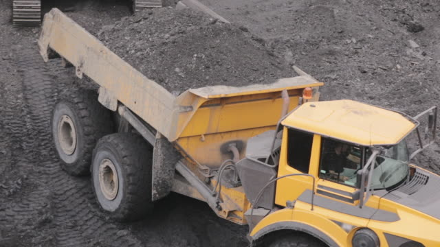 A mining truck is carrying coal A mining truck is carrying coal. Open pit coal mining dump truck stock videos & royalty-free footage