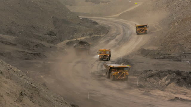 Mining trucks at a coal mine A wide shot of truck driving down a dusty road at an open-pit coal mine in Australia. coal stock videos & royalty-free footage