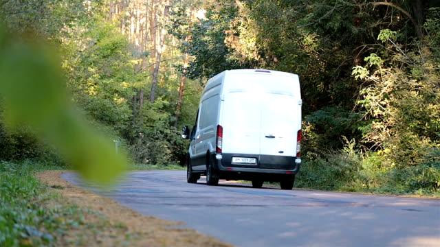 minivan fährt entlang des waldweges. - van stock-videos und b-roll-filmmaterial