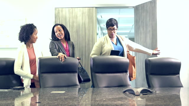 Minority businesswomen enter board room for meeting video