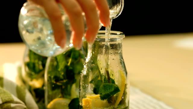 vídeos de stock e filmes b-roll de mint lemonade organic beverage pour water bottle - limonada tradicional