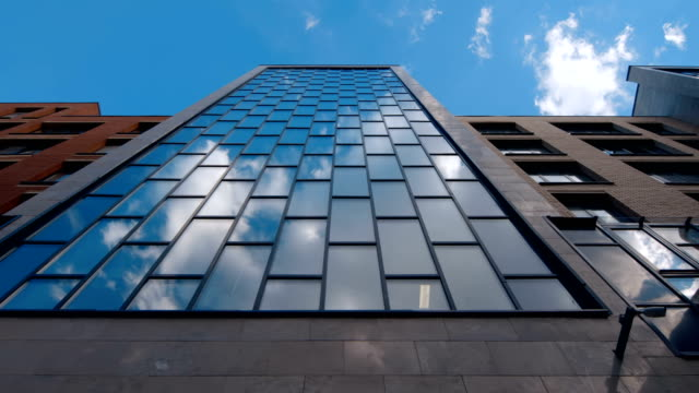 Mirror reflection in the glass surface of a skyscraper blue sky with clouds