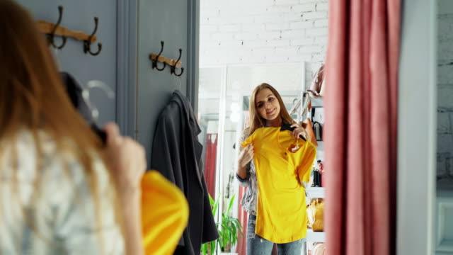 Tiro de joven eligiendo ropa en sala de montaje del espejo. Niña trata de tapa y puente, comprobar su tamaño y longitud estando enfrente del espejo grande. - vídeo