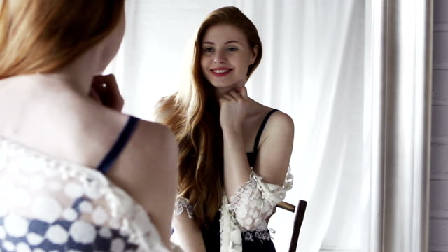 Mirror vanity   GL Dolly, slow motion video clip of a very beautiful young woman checking herself out & posing in a large mirror, she's wearing retro clothes & smiling & confident while being delighted by her appearance. She looks stunning & very attractive. vanity stock videos & royalty-free footage