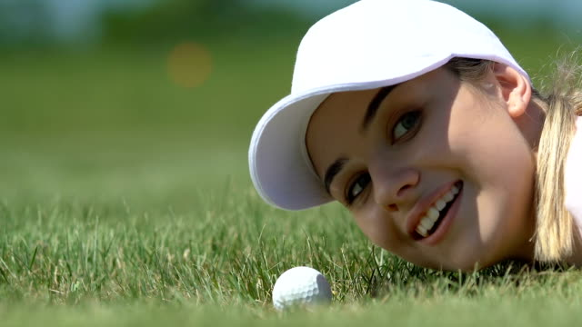 Mischief girl hitting golf ball into hole with fingers, having fun, close-up