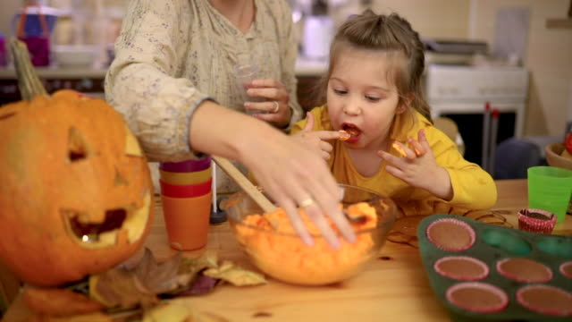 vídeos y material grabado en eventos de stock de chica travesura lamiendo sus dedos mientras prueba una glaseado naranja para la decoración de cupcake de halloween - halloween covid
