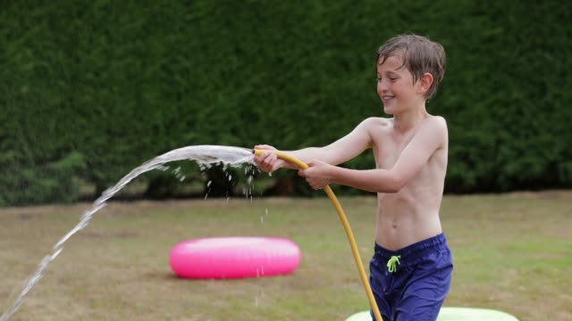 mischievous boy spraying water - tubo flessibile video stock e b–roll