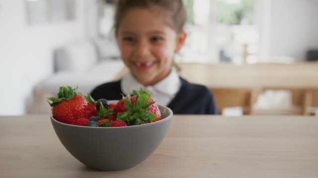 Mischievous Girl Wearing School Uniform Taking Strawberry From Kitchen Counter Mischievous girl in school uniform appears from behind kitchen counter and takes strawberry from bowl - shot in slow motion elementary age stock videos & royalty-free footage