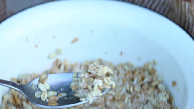 Miserable elder wrapped in warm plaid eating oatmeal porridge, social help