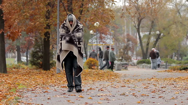 Miserable poor man walking in city park covered from cold with shabby blanket video