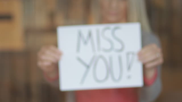 Miss You Sign During Airborne Illness Crisis Mature Female Shelter At Home During Quarantine Handheld Signs 4K Video Series Mature Female Shelter At Home Quarantine Set of Handheld Signs During the COVID-19 Crisis Part of a Sign Message Variation Series (Video Shot 4K rendered DaVinci Resolve 25 FPS second clips) stay home stock videos & royalty-free footage