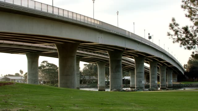 Mission Bay bridge at dawn Shot from below a bridge crossing a bay at sunrise cement stock videos & royalty-free footage