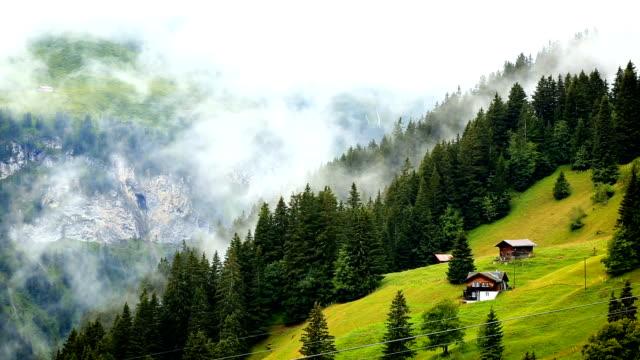 vídeos de stock e filmes b-roll de mist rising over swiss cottage in the alps - suíça