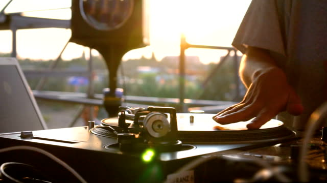 mix and scratch, hands of a dj on vinyl and mixer knobs. slow motion 120 fps. shooting with gimbal. sunset - giradischi video stock e b–roll