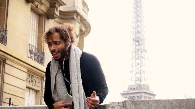 Mix blood music lover enjoying new earphones and smartphone  near Eiffel towe video