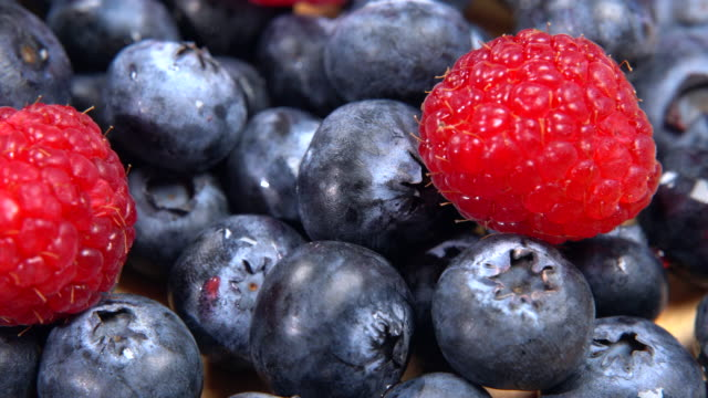 Mix of different fresh berries rotating on plate. Ripe blackberries and raspberries, close-up of forest fruit full of vitamins. Healthy eating and lifestyle