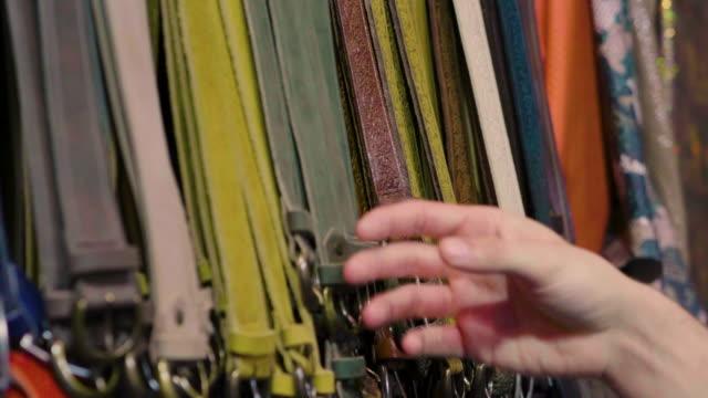 stockvideo's en b-roll-footage met een mix van leder en leren riemen in verschillende kleuren en een hand die aanraakt om de kwaliteit van het materiaal te testen. - dierenhuid huid