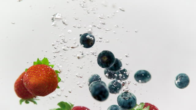 mixed berries spashing in refreshing water - bacca video stock e b–roll