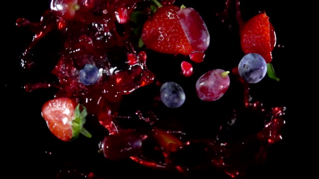 Mixed berries with juise flies to the camera