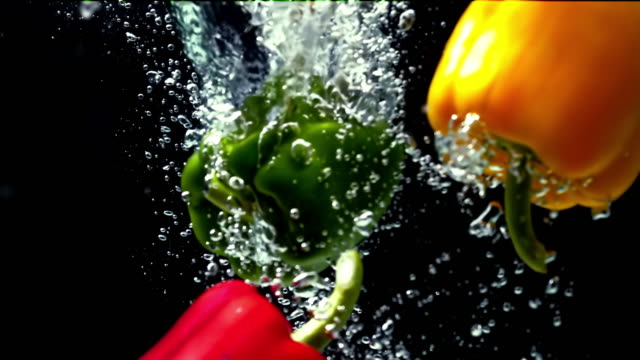mixed colored paprika falling into water on black background super slow motion 1000 fps - paprica video stock e b–roll