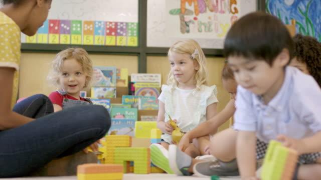 vidéos et rushes de étudiants d'âge préscolaire ethniques mélangés dans la garderie - enfant d'âge pré scolaire