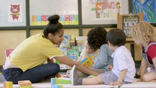 vídeos y material grabado en eventos de stock de estudiantes de preescolar étnico mixto en guardería - cuidado infantil