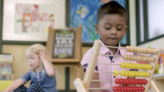vidéos et rushes de étudiants d'âge préscolaire ethniques mélangés jouant dans leur salle de classe - enfant d'âge pré scolaire