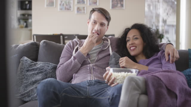 DS Mixed ethnicity couple watching TV and eating popcorn Medium dolly shot of a mixed ethnicity couple sitting on the sofa, watching TV and eating popcorn. Shot in Slovenia. young couple stock videos & royalty-free footage