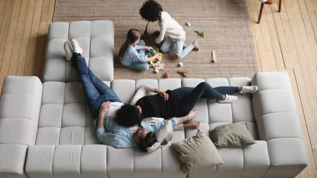 Mixed ethnicity parents with kids relaxing at home, top view Mixed ethnicity parents relaxing on comfortable couch while cute diverse kids daughters playing on floor at home. Interracial family with two children spending time together in living room. Top view domestic room stock videos & royalty-free footage