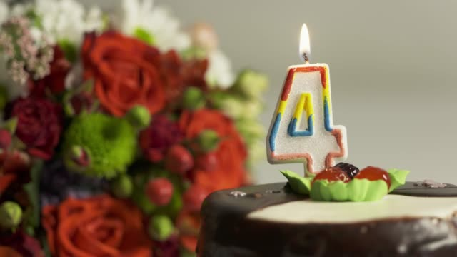 Mixed flower arrangement and birthday cake with burning candle number 4