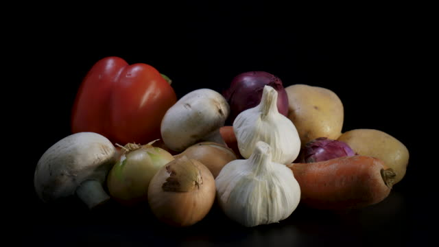 mixed fresh organic vegetables rotate against black background - aglio cipolla isolated video stock e b–roll